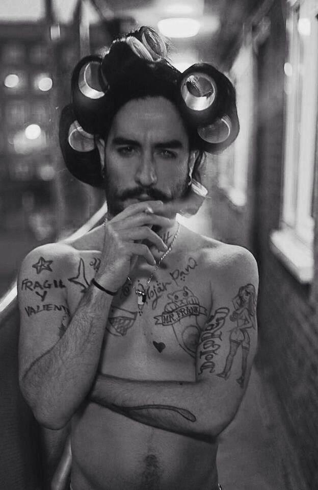 tattooed man in curlers
